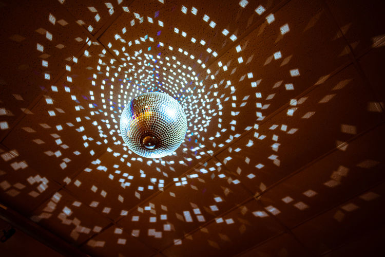 Low angle view of illuminated disco ball hanging from ceiling in nightclub
