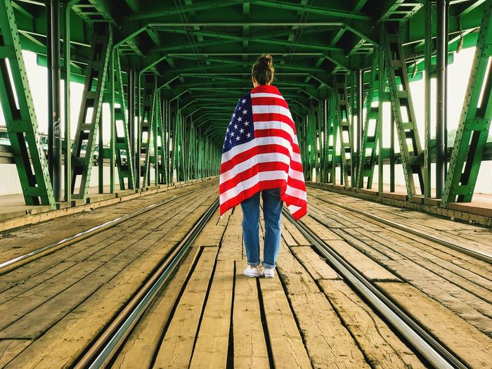 Bridge - Man Made Structure One Person Transportation Casual Clothing Built Structure Footbridge Wood - Material Lifestyles Architecture One Woman Only Women USA Flag American Flag America Independence Day 4th Of July July4th Flags Patriotism Patriotic Flags In The Wind  Symbol Arch Architecture Done That.