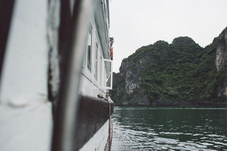 Ship sailing on sea against mountain