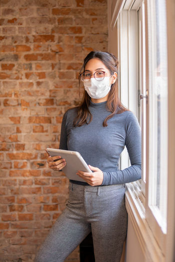 Woman holding smart phone while standing against brick wall