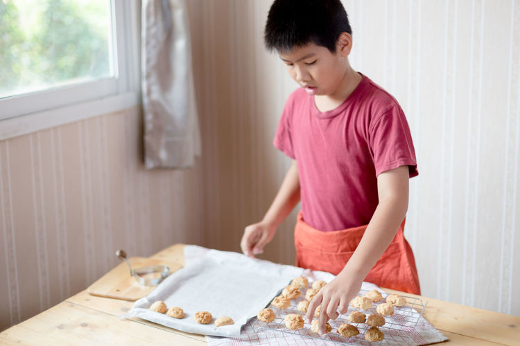 Boy Placing Food On Cooling Rack At Table
