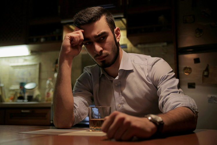 Sad Businessman Drinking Whiskey While Sitting At Table In Kitchen