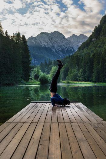 Man practicing yoga on lake against mountain