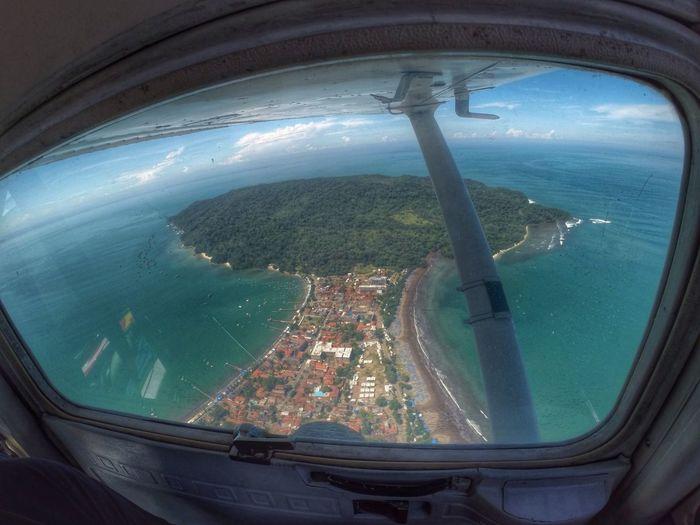 High Angle View Of Island Seen Through Airplane Window