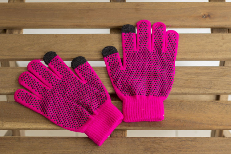 Directly above shot of pink gloves on wooden table