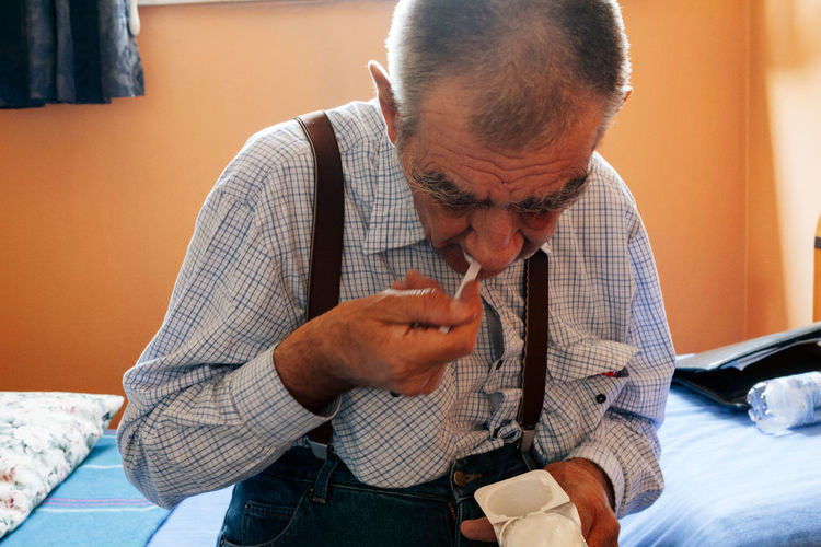 Close-up of old retired man sitting alone on a bed under the window eating a yoghurt