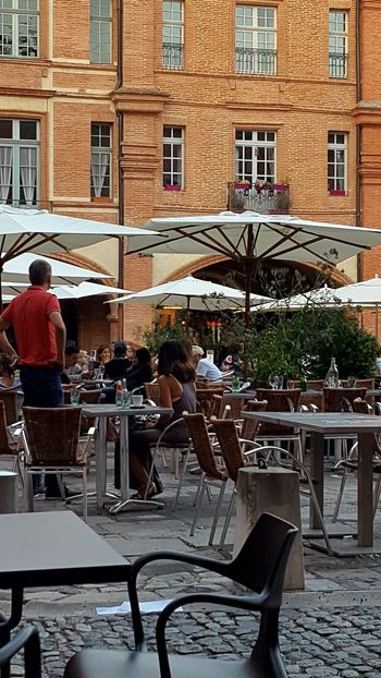 Men Chair Table Sitting Building Exterior Architecture Built Structure Lifestyles Person Leisure Activity Relaxation Place Setting Restaurant Holding Casual Clothing Day Market Vendor Outdoors Battle Of The Cities Montauban France Weekend Activities Cellphone Photography Model Outdoor Restaurant