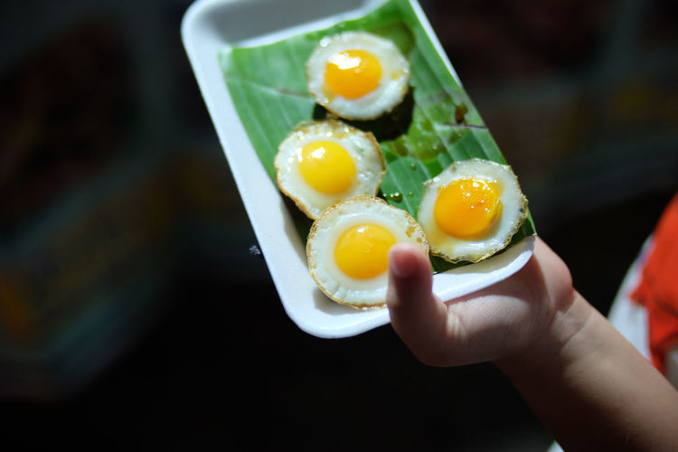 Close-Up Of Chid's Hand Holding Fried Eggs