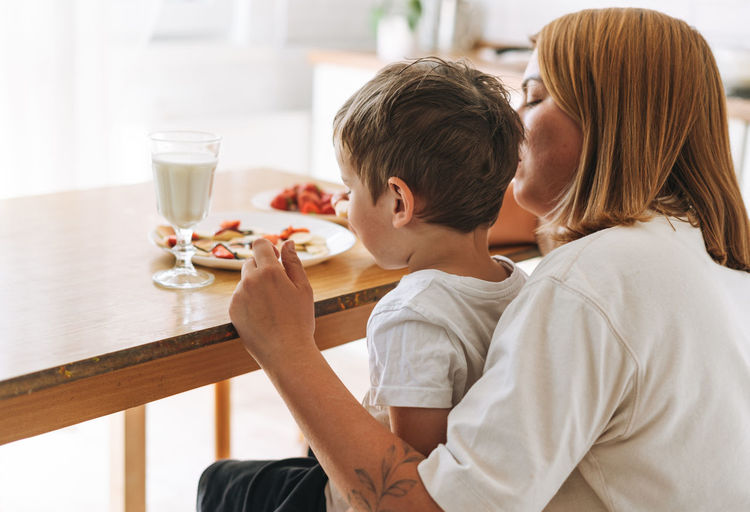 Cute toddler boy with his mother having breakfast with puncakes and berries in bright kitchen