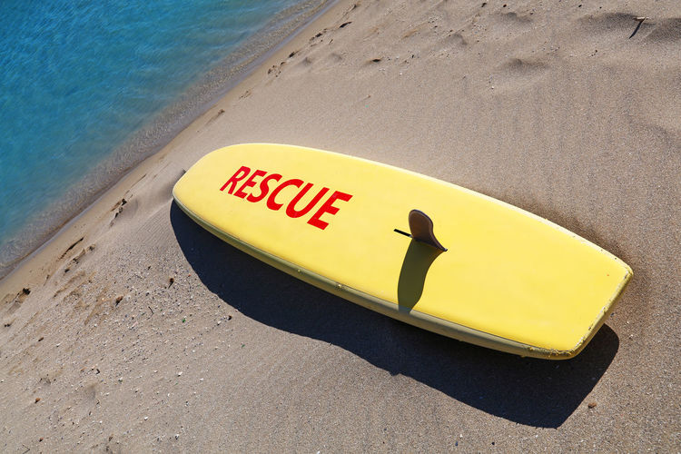 High angle view of yellow surfboard with rescue text at beach