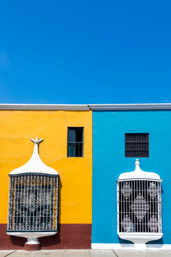 Blue and yellow houses against clear sky on sunny day