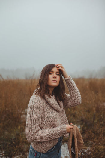Beautiful young woman looking away on field against sky