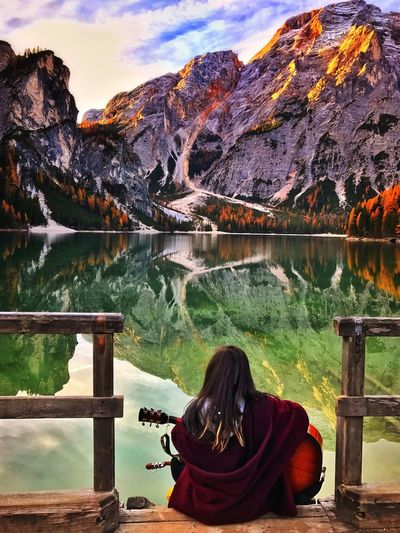 Young woman playing guitar in front of the mountains