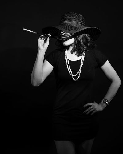 Young Woman Wearing Hat Standing Against Black Background