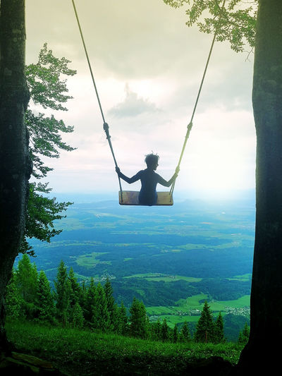 Scenic view of swing in park against sky