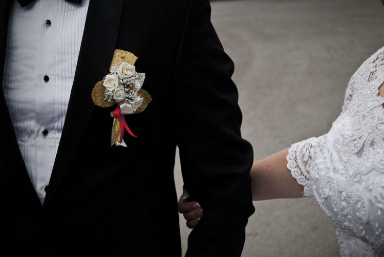 Midsection of bride and groom during wedding