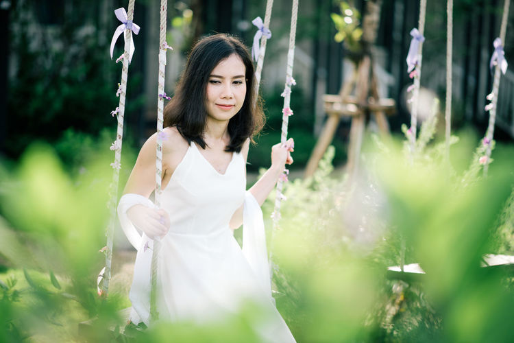 Women wear white dress. Adult Beautiful Woman Beauty Contemplation Day Fashion Flowering Plant Hair Hairstyle Holding Leisure Activity Long Hair Nature One Person Outdoors Plant Selective Focus Standing Three Quarter Length White Color Women Young Adult Young Women