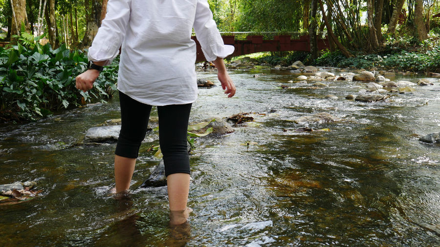 Full length of woman standing by river in forest