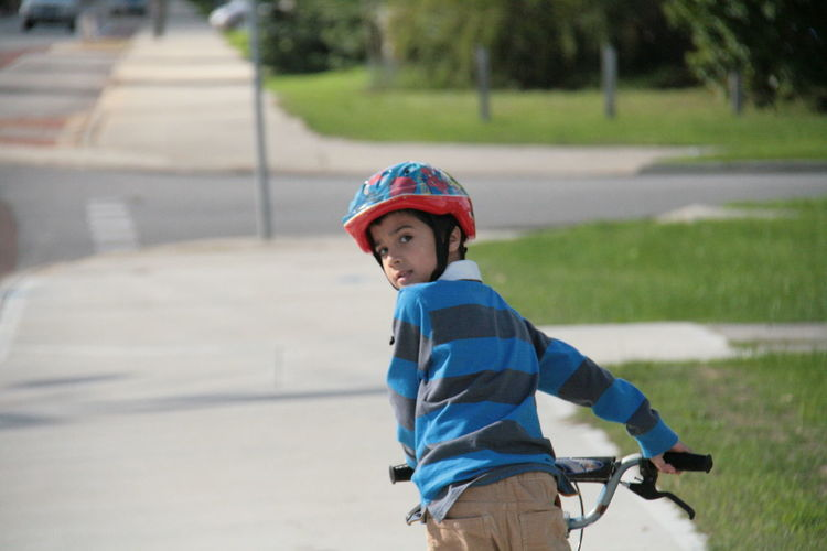 Portrait of boy riding bicycle on road