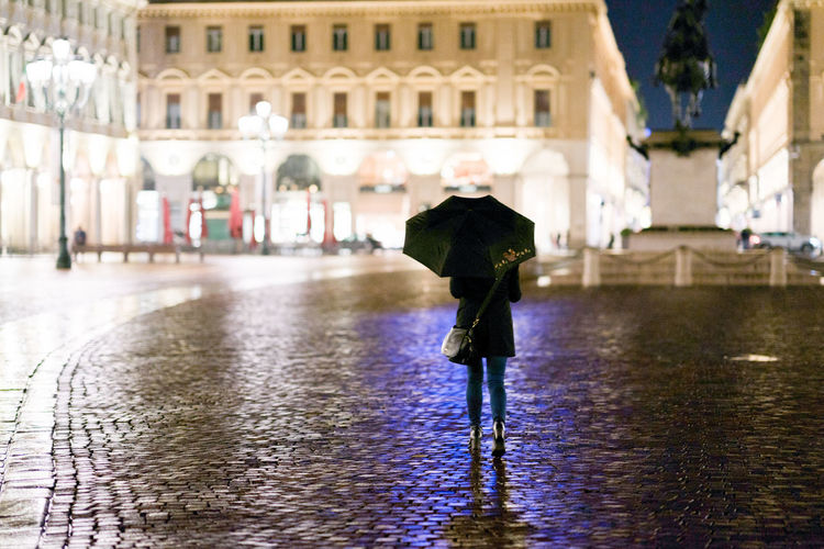 Rainy night in the city of turin Torino Architectural Column Warm Clothing Outdoors Rainy Season Protection Water Clothing Street Building Rear View Walking Women Umbrella One Person Full Length Rain Real People City Wet Built Structure Building Exterior Architecture Mirkomacaritorino