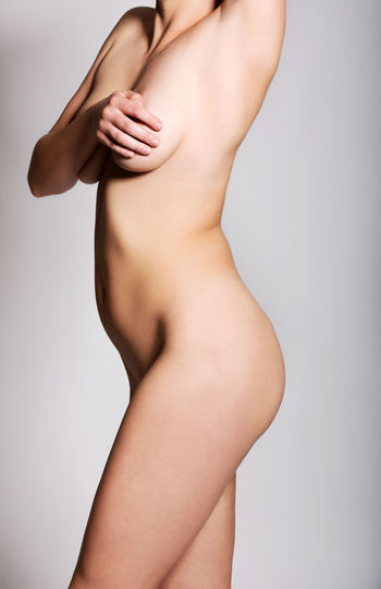 Midsection of shirtless woman covering breast against gray background