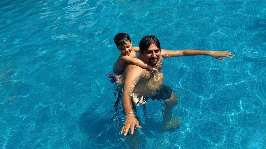 Portrait of father with son swimming in pool