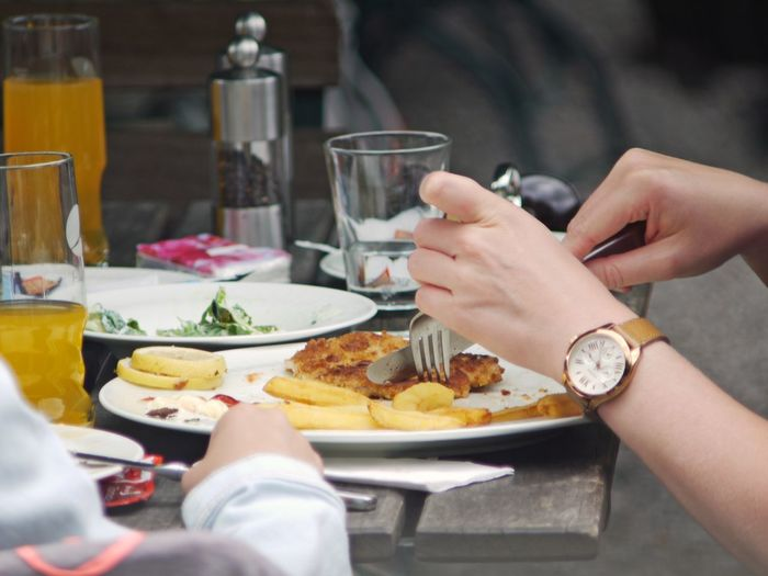 Close-up Day Drink Drinking Glass Eating Eating Food Food And Drink Fork French Fries Freshness Holding Human Body Part Human Hand Meal Outdoors People Plate Ready-to-eat Real People Schnitzel Summertime Table Women Wooden Desk