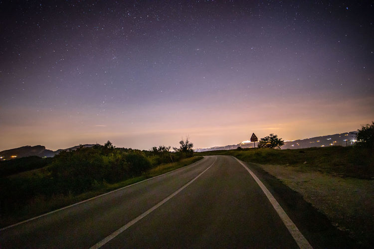 Road amidst landscape against sky at night