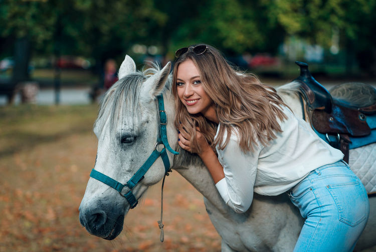 Portrait of woman standing by horse outdoors