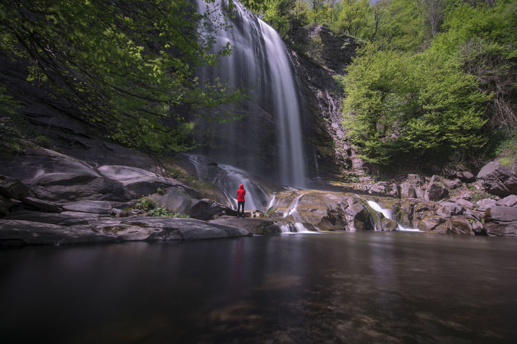 Woman looking at waterfall in forest