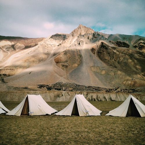 View of tents on field with mountains in background