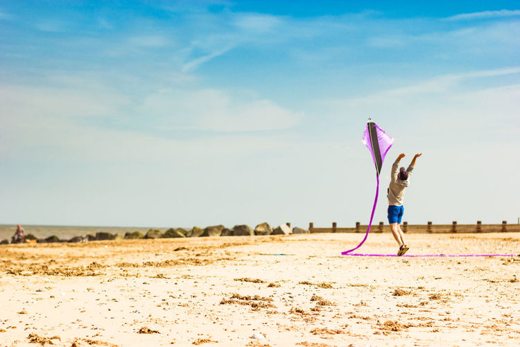 Man flying kite against sky during sunny day