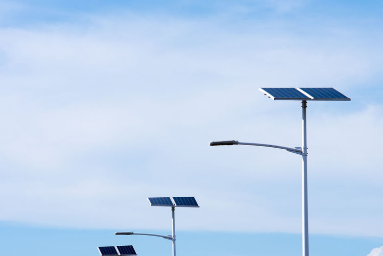 Low angle view of street light with solar panels against sky