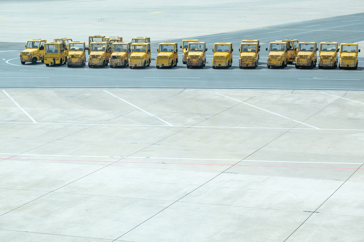 Copy Space In A Row Road Runway Traveling Airport Airport Departure Area Airport Waiting Architecture Business Day Empty Freight Transportation High Angle View Industry Land Vehicle Large Group Of Objects Mode Of Transportation No People Outdoors Road Marking Side By Side Transportation Truck Yellow Color