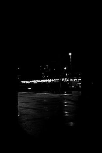 Illuminated street by city at night