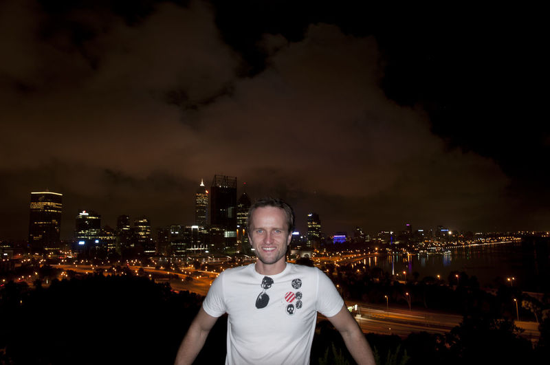 Portrait of young man standing against illuminated cityscape against sky at night