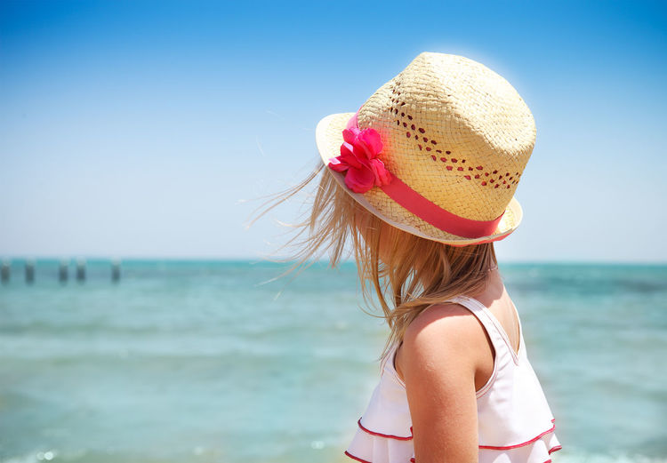 Girl wearing sun hat at beach during sunny day
