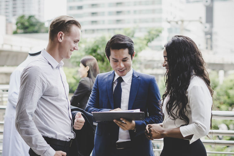 Business people discussing over file while standing outdoors