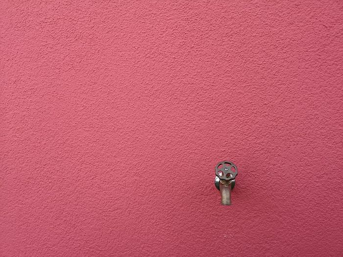 Bronze colored faucet with screw thread on a reddish magenta colored wall. Structure Wheel Brass GunMetal Copper  Reddish Magenta Bronze Faucet Screw Thread Wall Façade Architectural Detail Architectural Building Water Simplicity Simplistic Simple Copy Space Pink Color Backgrounds Full Frame Pink Background Textured  Purple Background Detail Pattern