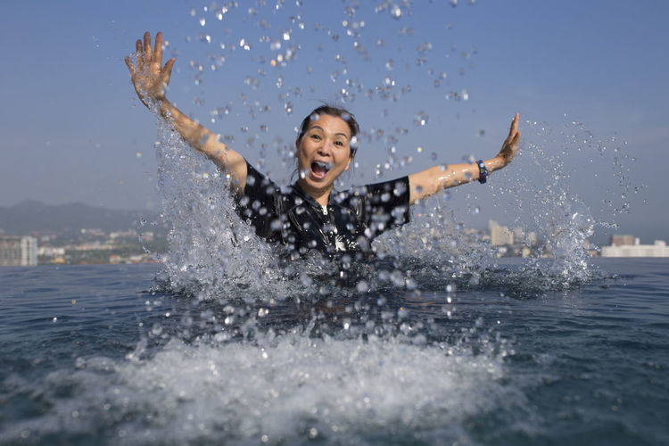 Adult Adults Only Arms Raised Carefree Cheerful Day Enjoyment Excitement Fun Happiness Human Body Part Laughing Leisure Activity Motion Nature One Person One Woman Only Only Women Outdoors Sea Sky Smiling Splashing Vitality Water