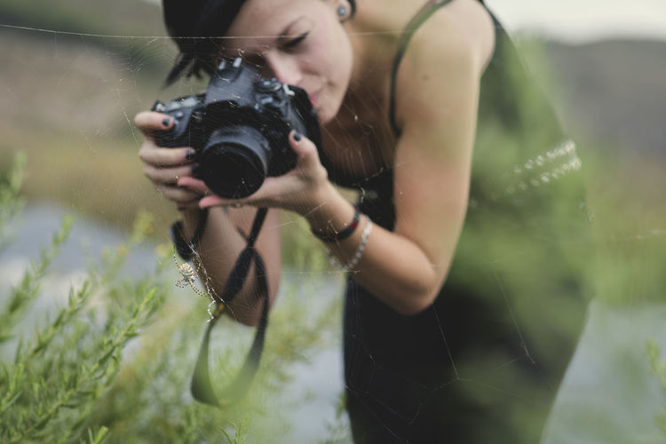 Woman photographing spider on web with camera