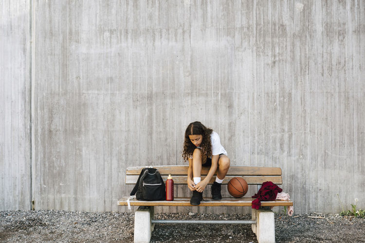 Young woman sitting on bench against wall