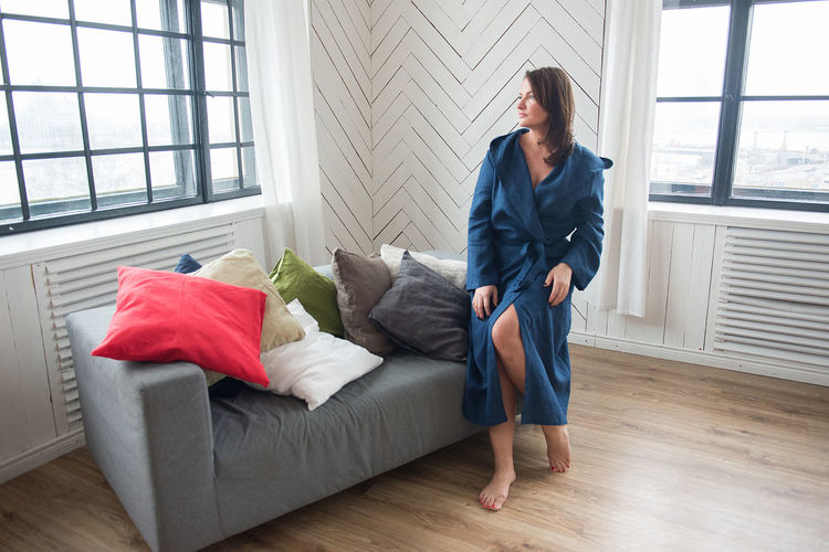 Fashion Morning Adult Adults Only Backgrounds Beautiful Woman Blue Day Domestic Life Dressing Gown Full Length Home Interior Indoors  Linen Living Room One Person One Woman Only People Pillows Real People Robe Sofa White Window Women