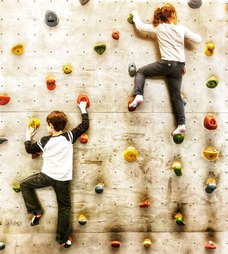 Full Length Of Siblings Climbing On Wall