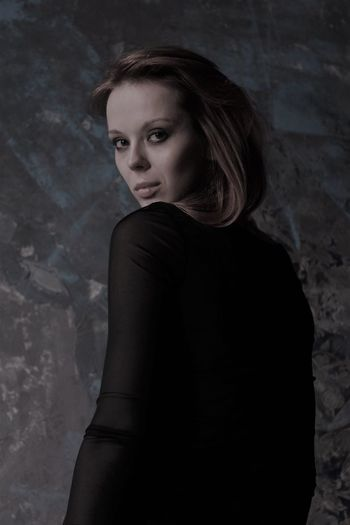 Portrait of woman looking over shoulder against wall