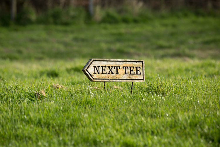 Vintage wooden Next Tee sign on a golf course. Arrow Caddie Field FreeTime Golf Golf Course Golf Game Golf Play Golfers Golfing Range Grass Green Nature Next Point Next Tee Outdoors Recreation  Recreation And Relaxation Sign Sign Post Sunny Day Vintage Sign Wooden Sign Wooden Signpost