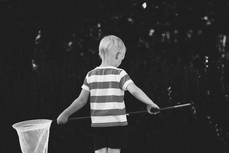 Rear view of boy holding umbrella