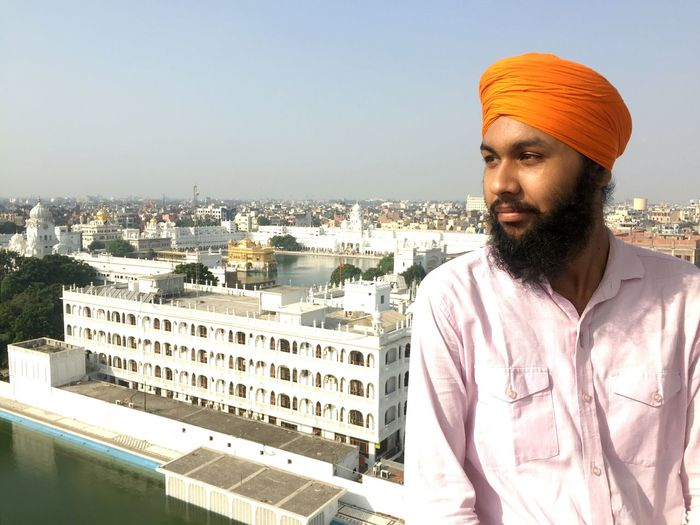 Man in turban standing against cityscape