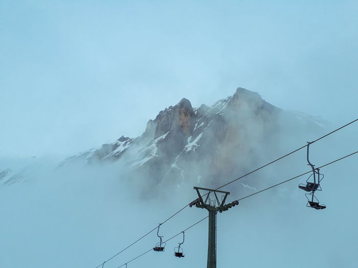Empty Snowboarding Skilift Mountain Winter Connection Communication Technology Outdoors Day Mountain No People Winter Nature Sky Cable Low Angle View Cold Temperature Beauty In Nature Power Line  Electricity  Fuel And Power Generation Scenics Fog Snow Electricity Pylon Ski Lift