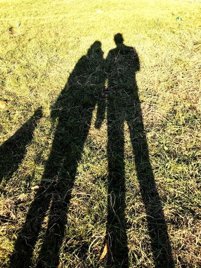 Shadow Real People Sunlight Two People Grass Lifestyles Togetherness Focus On Shadow Leisure Activity Bonding Friendship Men Day Forming Outdoors Low Section Nature Human Body Part Mammal
